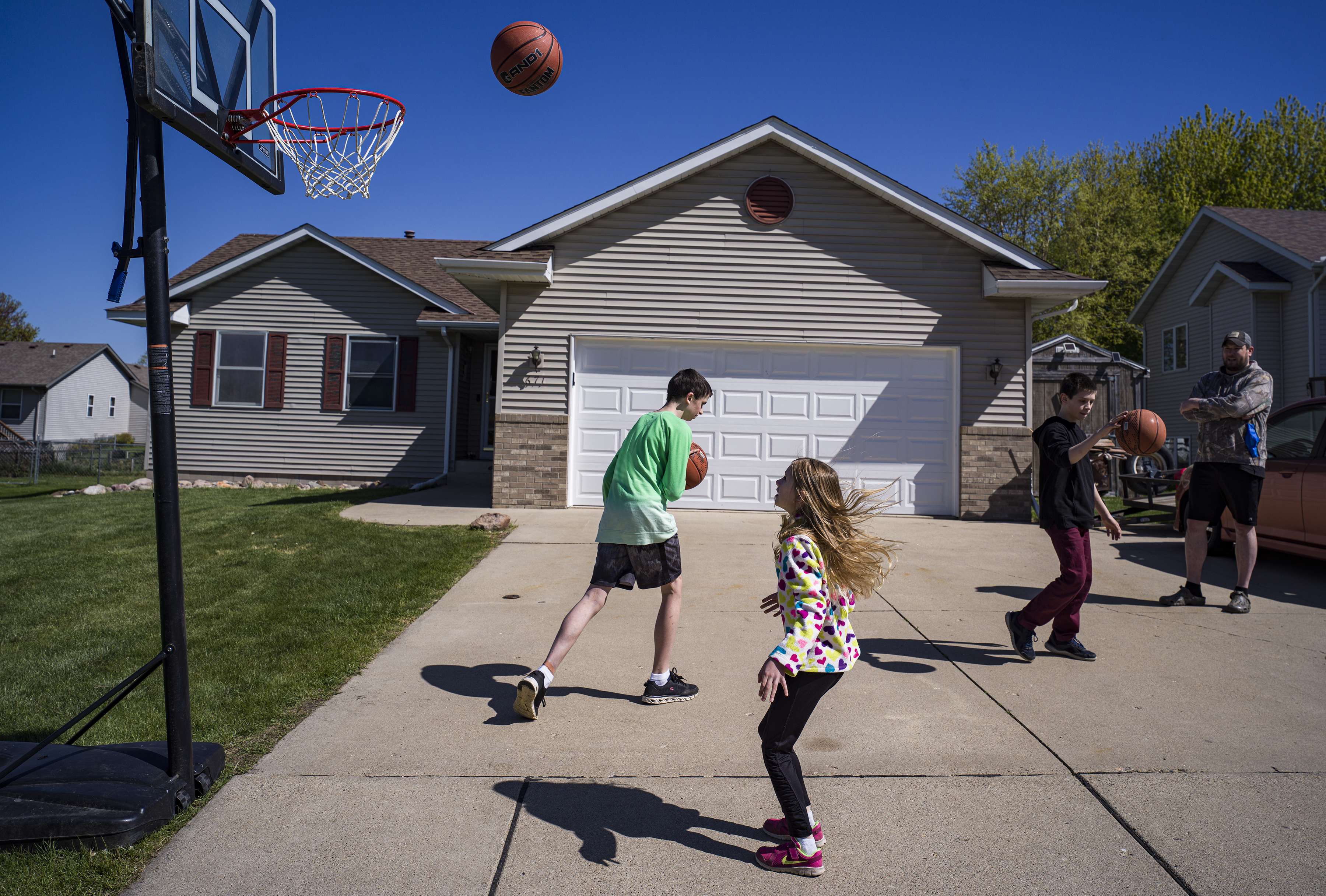 In Owatonna, MN on May 12, 2021, the Hadt siblings Abigail, 7, Carter, 11, Riley,14(green) play some hoops during recess while dad Andrew watches.